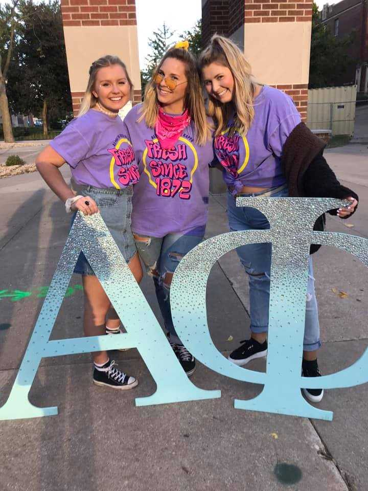 Members of Alpha Phi pose with their giant letters in front of the clock tower, celebrating their 2018 Bid Day.