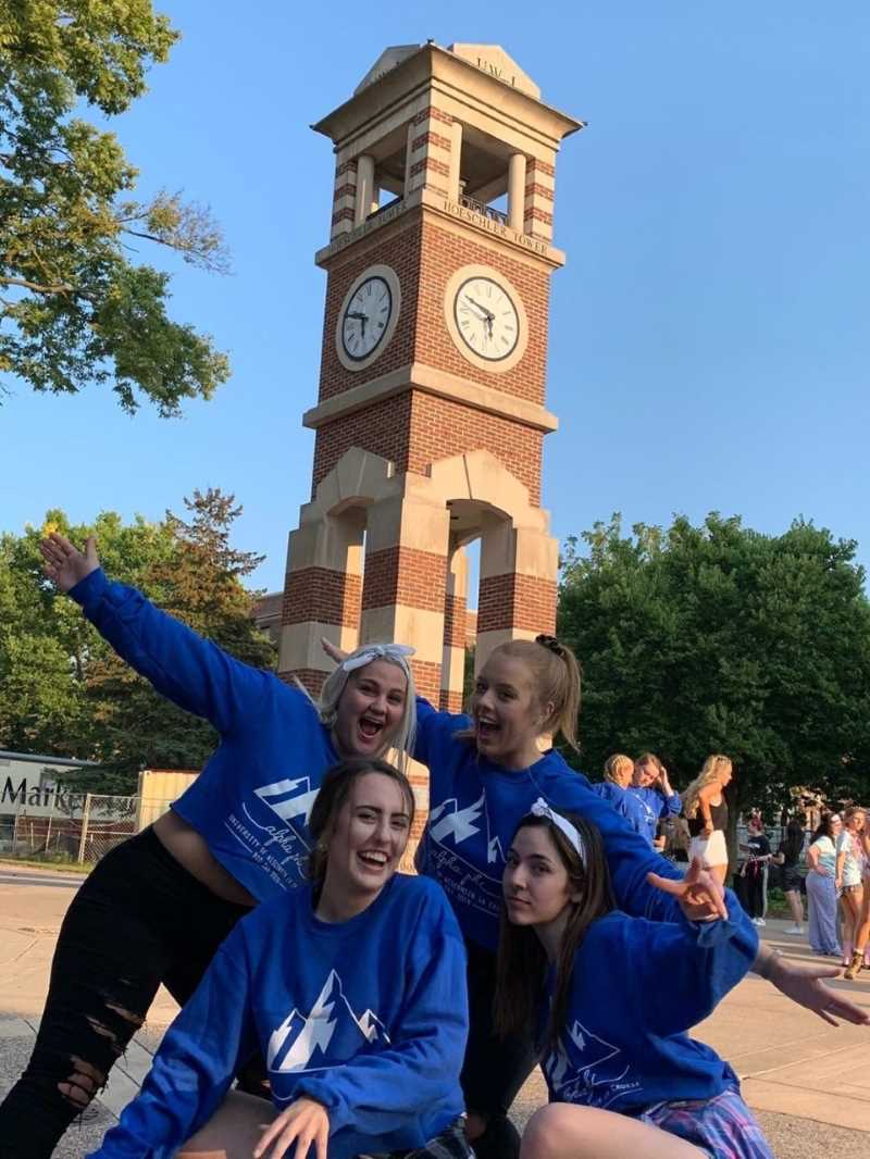 A group of Alpha Phi members pose in front of the clock tower in their matching bid day sweatshirts.