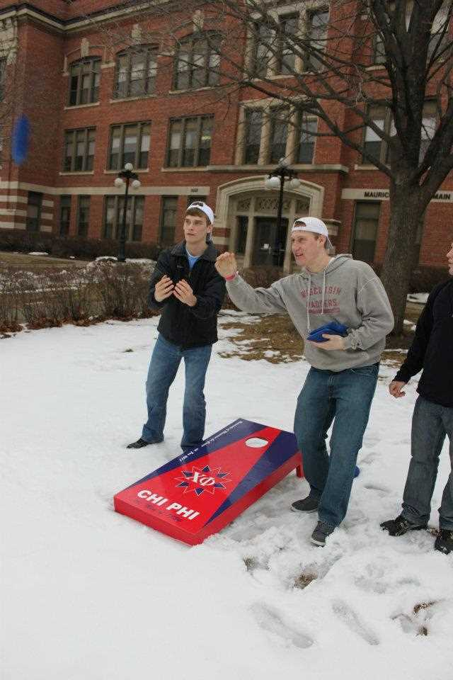 Two members of Chi Phi play bag toss outside in the snow.