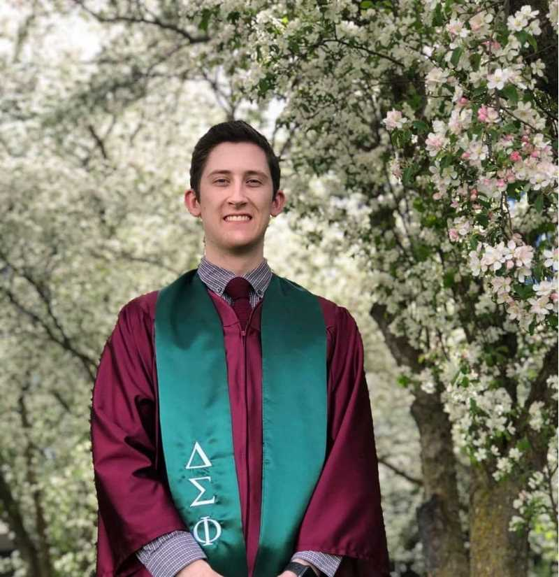 A fraternity member has his photograph taken wearing the Delta Sigma Phi graduation stole.