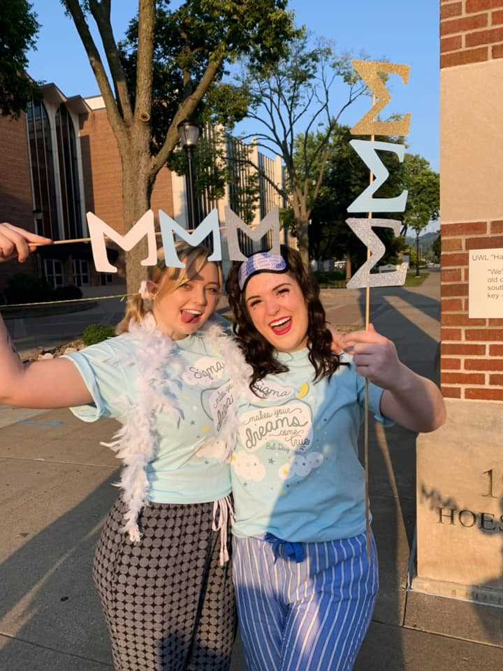 Two Tri Sigma women celebrate 2019 Bid Day waving their letters and wearing matching Bid Day shirt.
