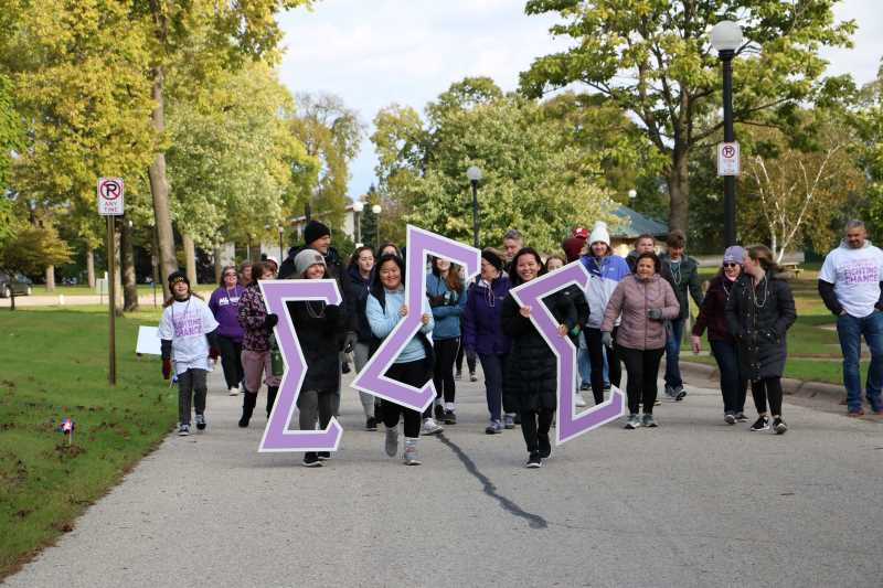 The women of Tri Sigma walk with their giant letters to spread awareness and raise money for their national philanthropy-- The March of Dimes.