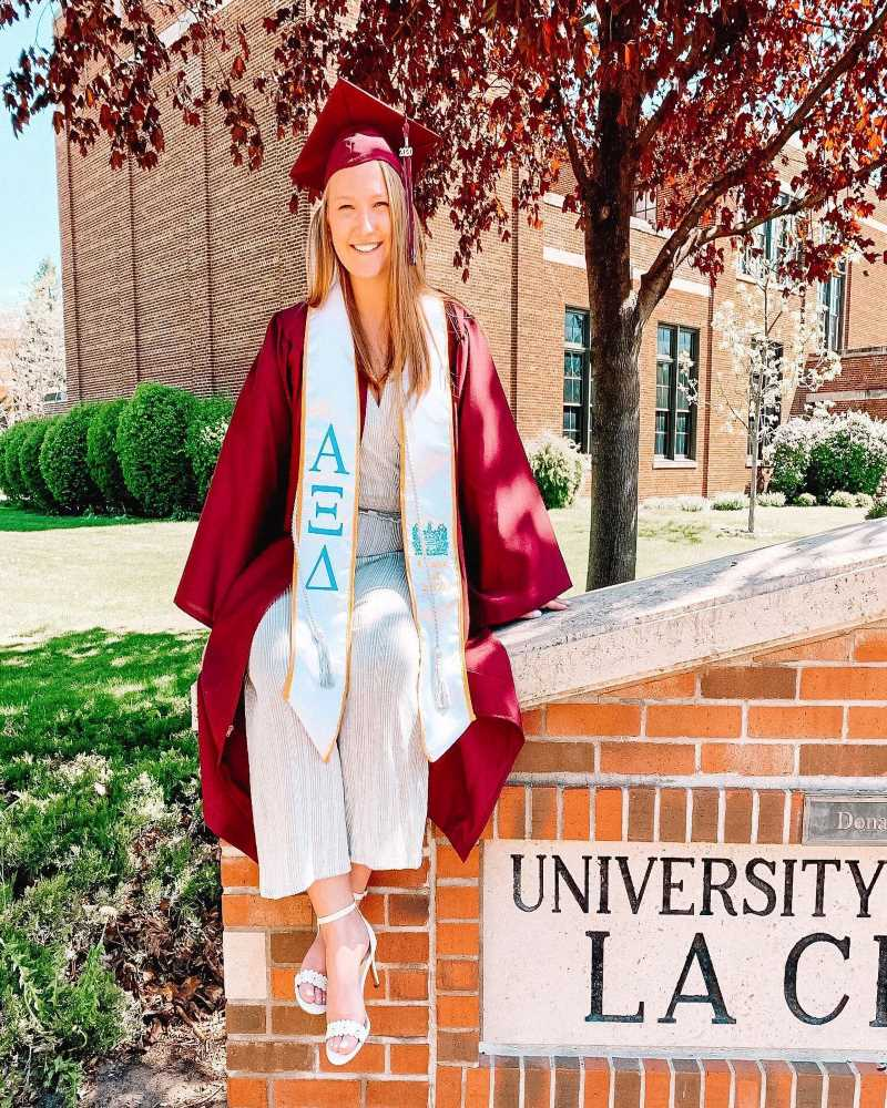 An Alpha Xi Delta woman poses in front of a university building wearing her cap and gown, and sorority stole.