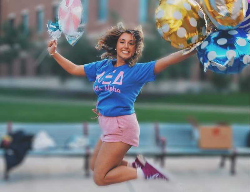An Alpha Xi Delta woman jumps for joy during the 2019 Bid Day celebration.