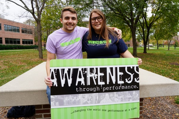 Two Students Holding an Awareness through Performance Sign