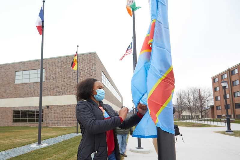 UWL Senior Vanessa Mbuyi Kaja raises the flag of the Democratic Republic of Congo for the first time on campus during a December 2020 ceremony. The flag's addition to the group of international flags on Badger Street was among the many accomplishments for the International Education & Engagement Office, which has received the state's 2021 Hong Rost Memorial Leadership Award for Innovation in International Education Student Services.