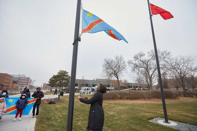 "UWL Senior Vanessa Mbuyi Kaja raises the flag of the Democratic Republic of Congo for the first time on campus during a December 2020 ceremony. ""I already knew I was accepted here in La Crosse, but this makes me feel like yes, I can call this my home,"" noted the microbiology major."