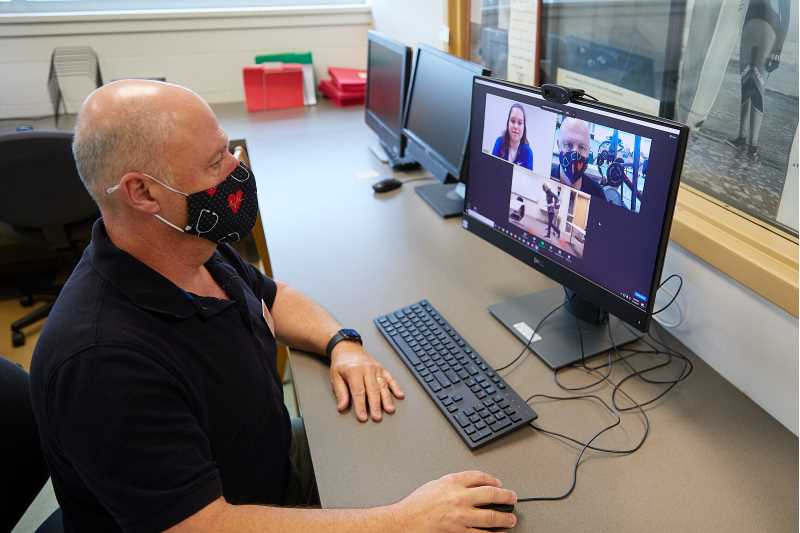 Associate Professor John Greany watches his students provide virtual rehabilitation services to local community members — part of UWL's Exercise Program for Adults with Neurologic Disorders. The assignment gave students firsthand experience within the growing field of telehealth.