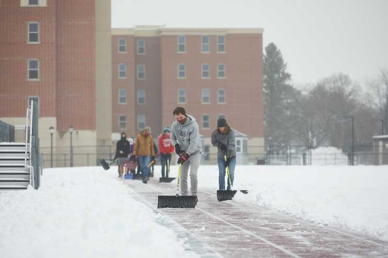 Student athletes from the Cross Country team shovel a few track lanes after a recent snow.