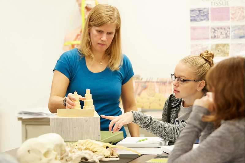 Lisa Kobs works with students in an Anatomy and Physiology classroom.