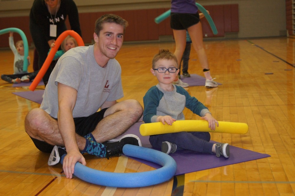 Adapted Physical Education Teaching Minor plays with a child with a disability in the gym.