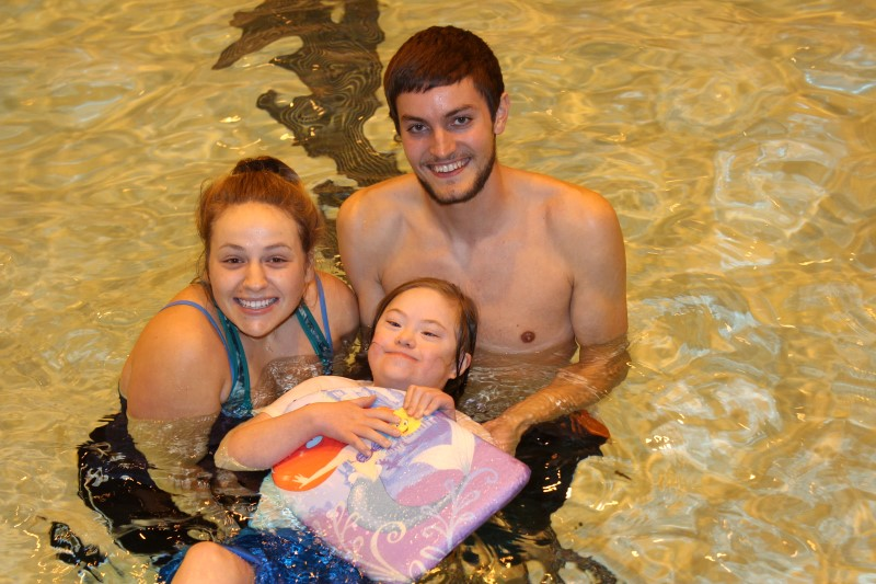 Two University Students help a girl with a disability float in the pool.