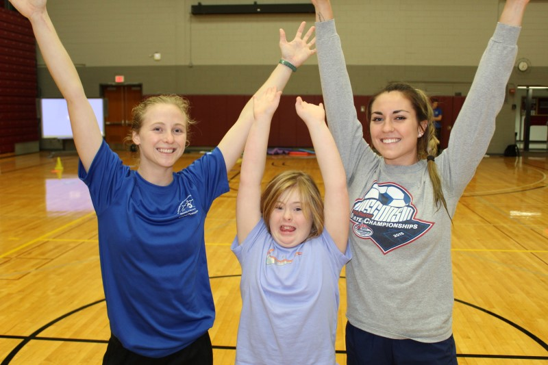 Two Physical Education Teaching Minors raise their hands to celebrate with a child with a disability.