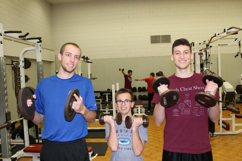 Two University Students lift weights with a boy with a disability.