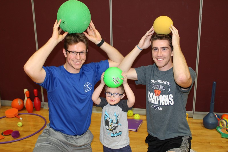 Two Adapted Physical Education Teaching Minors and a child with a disability hold their balls above their heads and smile.