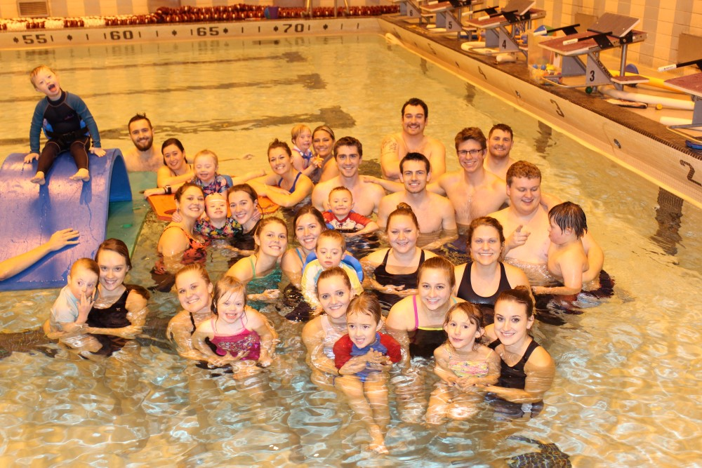 A group of Adapted Physical Education Teaching Minors and children with disabilities pose for a picture in the pool.