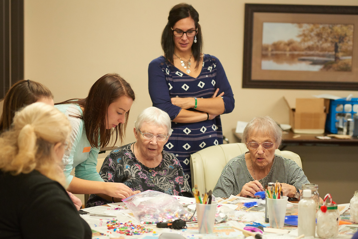 Lindsey Kirschbaum, an associate lecturer in the Recreation Management and Therapeutic Recreation Department, oversees students in her therapeutic recreation class working with residents in a La Crosse manor.