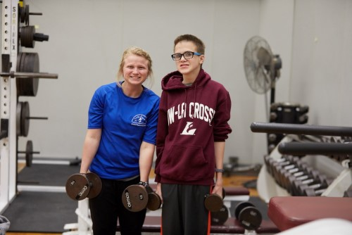 Graduate student lifts weights with Motor Development participant