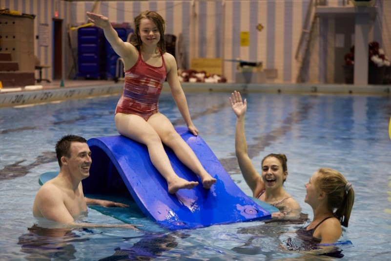 Graduate students work with children in the pool