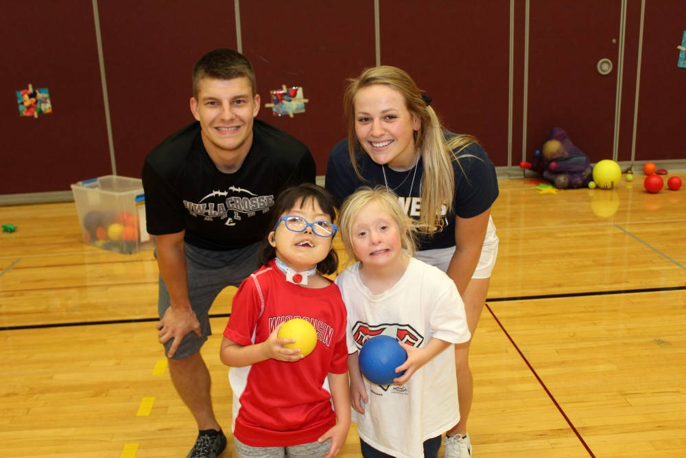 Two Adapted Physical Education Minor students play ball with two girls with disabilities.