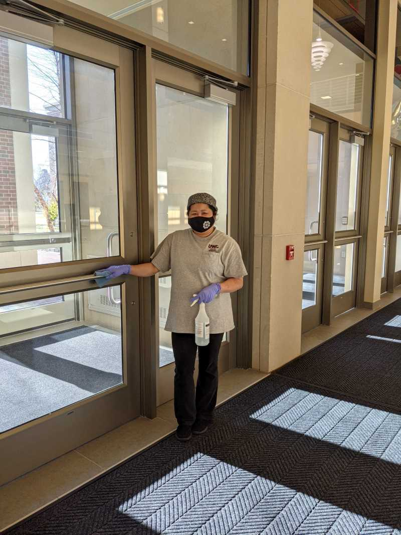 Amee Thao, a custodial staff member ensuring high touch points like doors are clean.